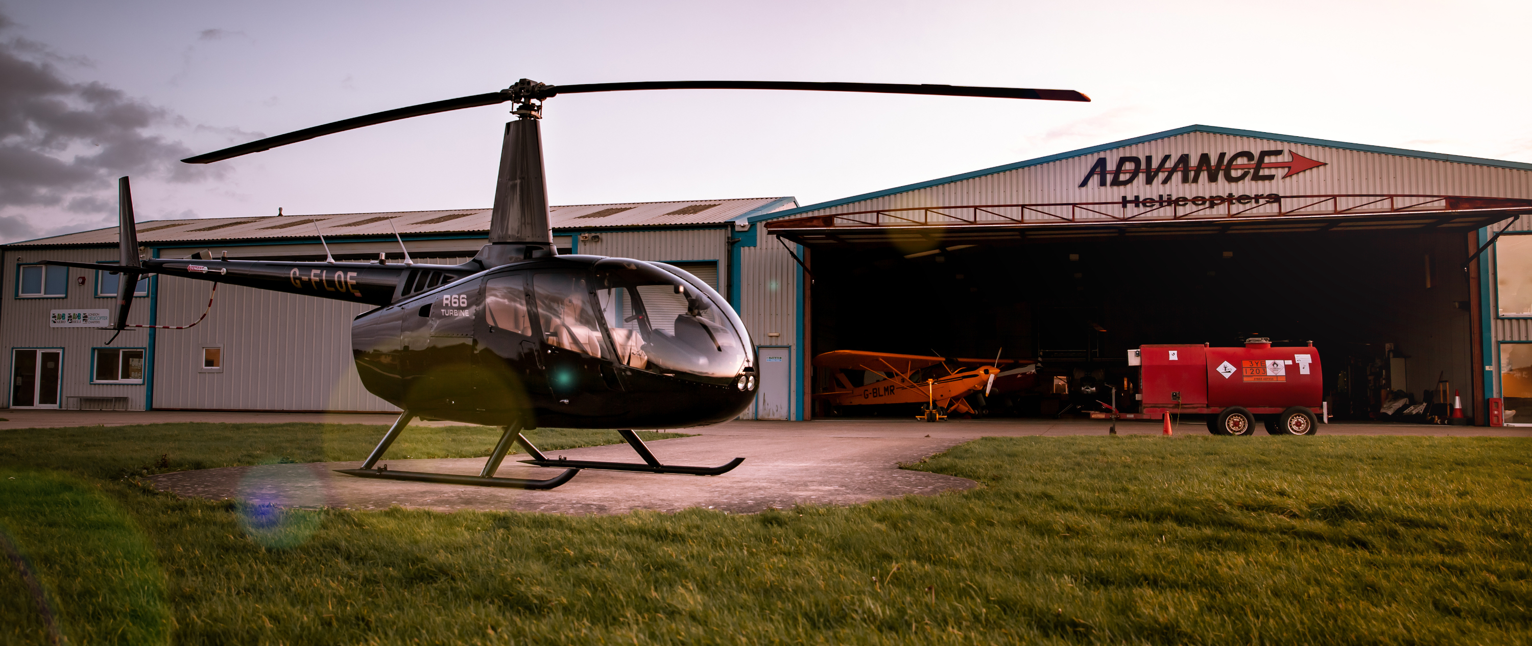 Robinson R66 turbine helicopter in front of Advance Helicopters hangar